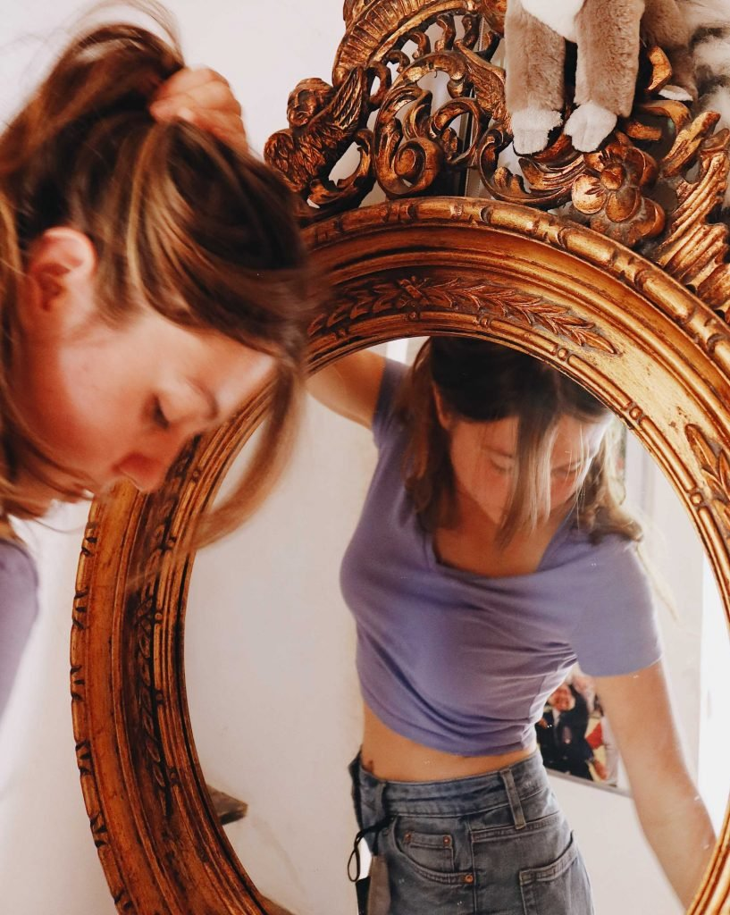 woman looking in mirror wearing jeans_revelle