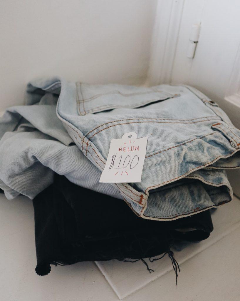 pile of folded jeans_best jeans under 100_revelle