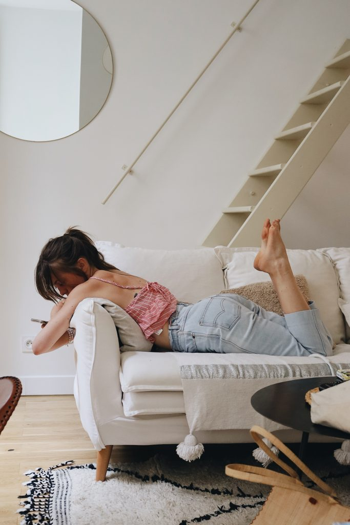 girl lounging on couch wearing jeans_comfortable jeans for women_revelle