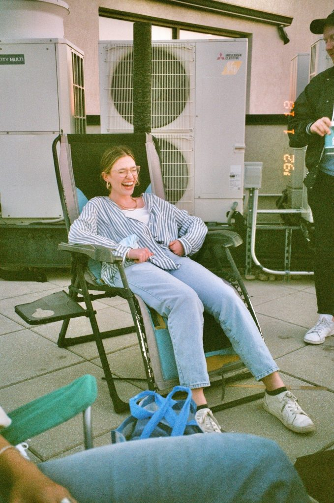 Woman lounging on chair laughing_katie paganelli_revelle