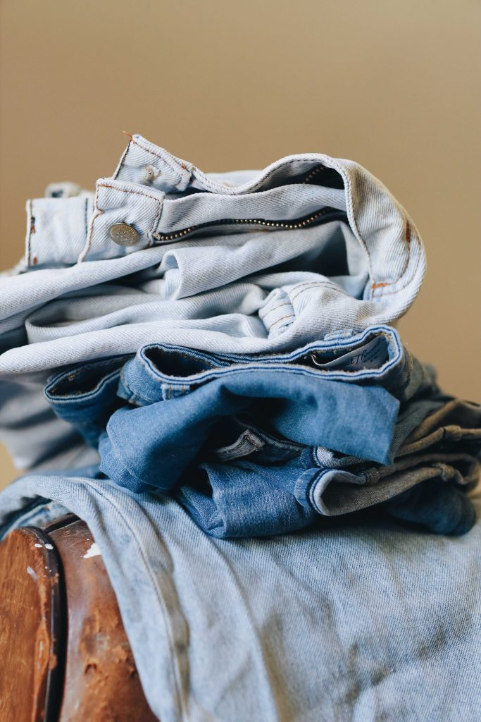 folded jeans stacked on couch_best blue jeans for women_revelle